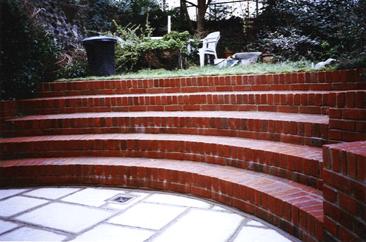 red brick curved steps in small brighton garden